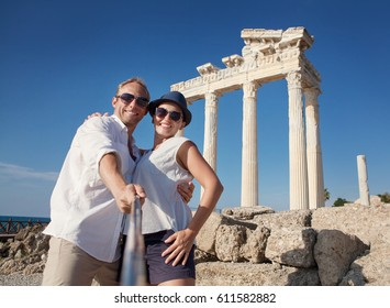 Smiling young couple take a selfie photo on antique ruins. Temple of Apollo, Side, Turkey