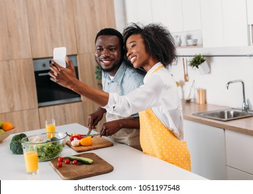 Smiling young couple taking selfie while cutting vegetables on board at table
