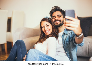Smiling young couple taking selfies