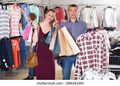 Smiling young couple and teen stands near clothes and choosing man shirt in shop