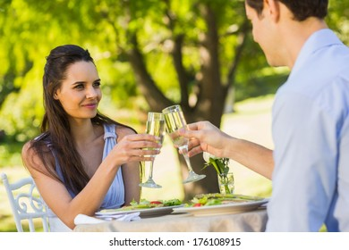 Smiling young couple toasting champagne flutes at an outdoor caf�©