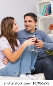 Smiling young couple toasting wine glasses on sofa at home