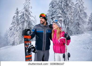 smiling young couple together skiing on snowy mountain and looking something in distance