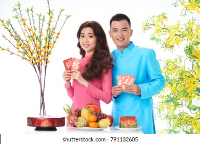 Smiling young couple in traditional dresses holding lucky money envelopes