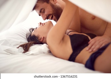 Smiling young couple in underwear having fun in bed
