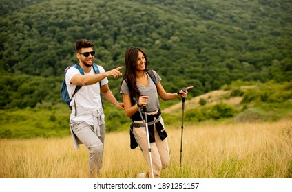 Smiling young couple walking with backpacks over green hills