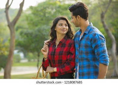 Smiling young couple walking outdoors with the man putting his arm around the woman looking at each other