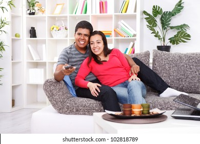 Smiling young couple watching TV on couch at home