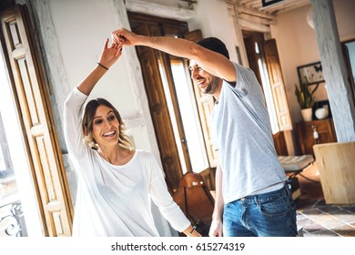 Smiling young couple wearing casual clothing spinning while dancing at apartment in daylight.
