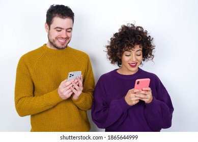 Smiling Young couple wearing knitted sweater standing against white background using cell phone, messaging, being happy to text with friends, looking at smartphone. Modern technologies and communicati