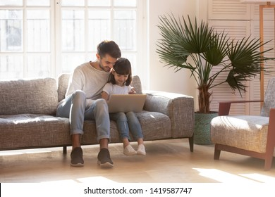 Smiling young dad sit on couch have fun using laptop with cute little daughter, happy father relax on sofa spend time at home with small girl child playing on computer or watching cartoon video