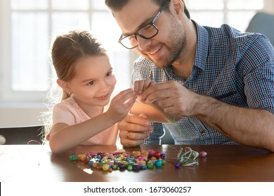 Smiling young daddy helping small preschool daughter making bracelets with wooden bead pieces at home, head shot. Happy little child girl involved in creative activity with father, sitting at table.