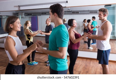 Smiling young dancing bachata in dance studio