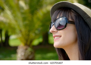 smiling young dark-haired woman with sunglasses in the park