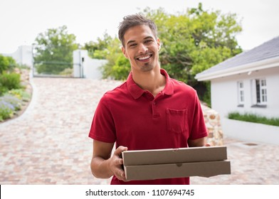 Smiling young delivery man holding pizza boxes outdoor. Happy deliveryman in red t-shirt holding two pizzas outside house. Portrait of satisfied guy delivering pizzas and looking at camera.