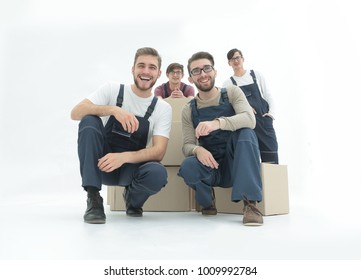 Smiling young delivery men holding stack of boxes. Isolated on w