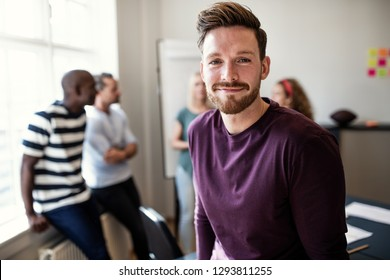 Smiling young designer standing in an office after a boardroom meeting with colleagues talking together in the background