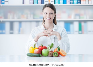 Smiling young dietician sitting at desk and showing colorful vegetables and fruit, healthy eating and diet concept