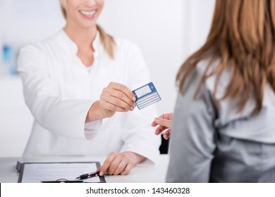 Smiling young doctor giving health card to a patient