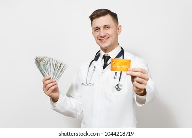 Smiling young doctor man isolated on white background. Male doctor in medical uniform, stethoscope holding bundle of dollars, banknotes cash money, credit card. Healthcare personnel, medicine concept