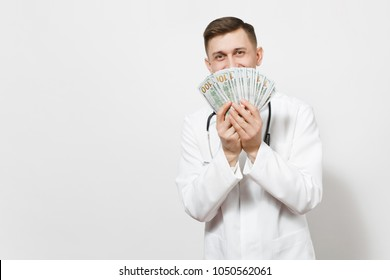 Smiling young doctor man isolated on white background. Male doctor in medical uniform, stethoscope holding bundle of dollars, banknotes, cash money. Healthcare personnel health, medicine concept