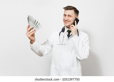 Smiling young doctor man isolated on white background. Male doctor in medical uniform talking on mobile phone, holding bundle of dollars, banknotes, cash money. Healthcare personnel, medicine concept