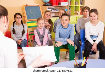 Smiling young elementary age children sitting and listening teacher at class
