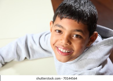 Smiling young ethnic school boy wearing grey sweater in classroom