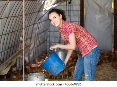 smiling young european woman farmer holding bucket with chicken forage in hen house