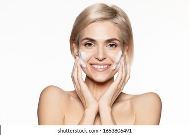 Smiling young european woman  lathering foam on cheeks washing face. Skincare and hygiene procedure. Closeup studio portrait on white copy space