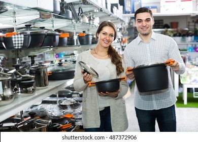 Smiling young family choosing new pans for home kitchen in shop cookware