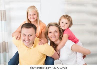 Smiling Young Family Enjoying Piggyback At Home