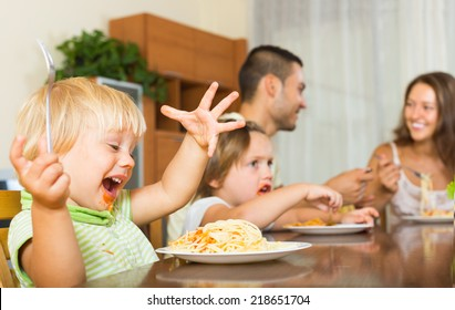 Smiling young family of four having lunch with spaghetti at home. Focus on girl