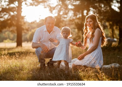 Smiling young family with little baby girl spending time together at the park, having a walk. Mom, dad and child playing outdoors at the sunset time. Concept of friendly family