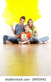 smiling young family painting interior wall of home.