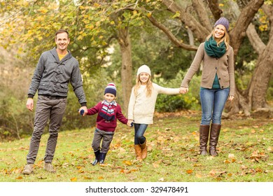 Smiling young family posing together on an autumns day
