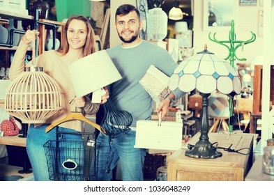 Smiling young family showing their buies in furnishings store