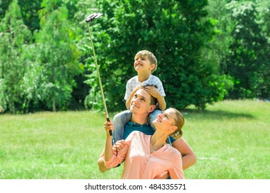 Smiling Young Family Taking Selfie In Park