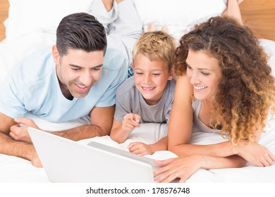 Smiling young family using laptop together on bed at home in bedroom