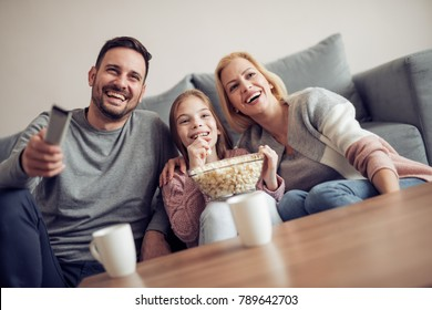 Smiling young family watching TV together.They are spending free time at home.