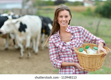 Smiling young farmer carrying bottles of fresh milk
