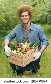 Smiling young farmer wearing straw hat and jean jacket, and looking at camera. Farmer holding wooden box with fresh vegetables