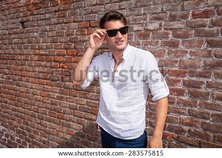 67afe5db7396 Smiling young fashion man looking away from the camera while fixing his  sunglasses.
