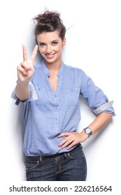 Smiling young fashion woman leaning on a white wall while showing the victory sign.