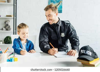 smiling young father in police uniform and son drawing together at home