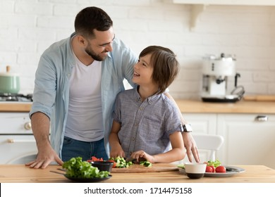 Smiling young father teaching little kid son chopping fresh vegetables for healthy vegetarian dinner, enjoying spending time together in kitchen. Happy child boy learning cooking with dad at home.