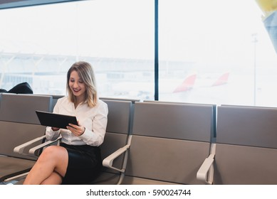 Smiling young female browsing tablet. Horizontal indoors shot.