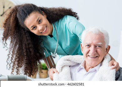 Smiling young female caregiver covering smiling old man with blanket