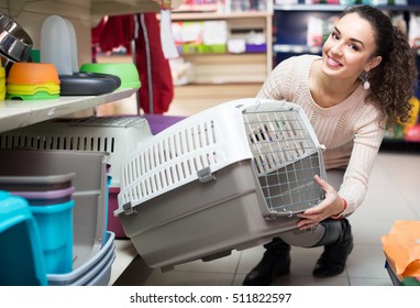 Smiling young female customer buying kennel for pet in shop
