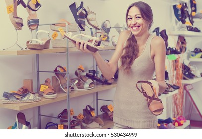 smiling young female customer choosing from two pair of shoes and buying in store